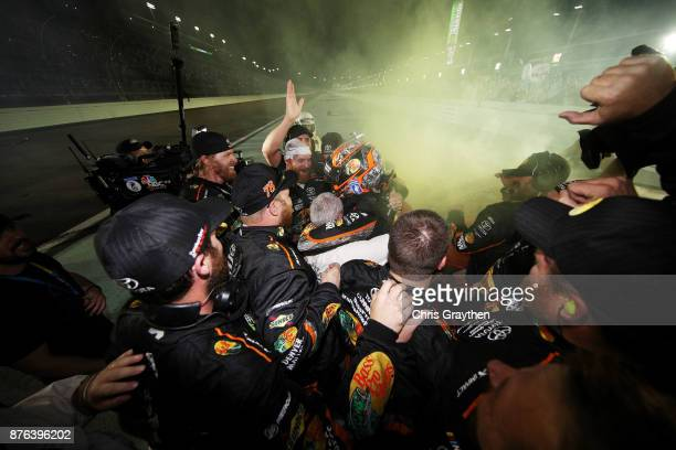 Martin Truex Jr driver of the Bass Pro Shops/Tracker Boats Toyota celebrates with teammates after he won the Monster Energy NASCAR Cup Series...