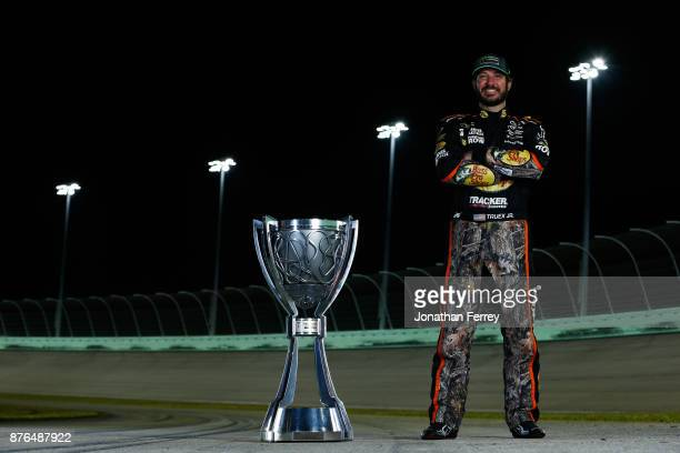 Martin Truex Jr driver of the Bass Pro Shops/Tracker Boats Toyota poses with the Monster Energy NASCAR Cup Series championship trophy after winning...