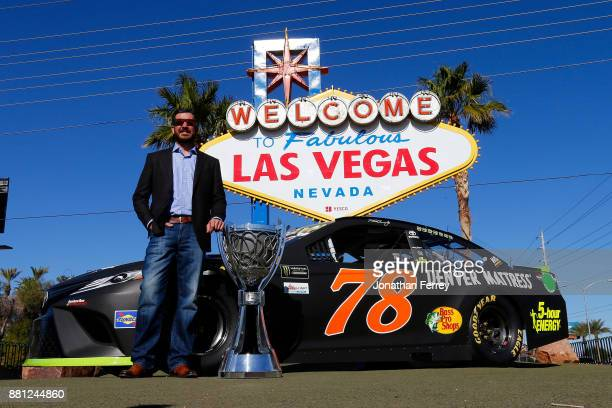 Martin Truex Jr driver of the Bass Pro Shops/Tracker Boats Toyota poses with the Monster Energy NASCAR Cup Series championship trophy in front of the...