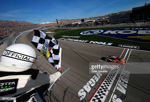 Martin Truex Jr driver of the Bass Pro Shops/TRACKER BOATS Toyota crosses the finish line to win the Monster Energy NASCAR Cup Series Kobalt 400 at...