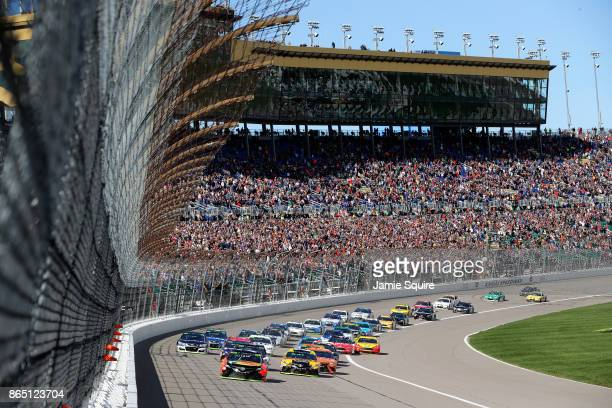 Martin Truex Jr., driver of the Bass Pro Shops/Tracker Boats Toyota, leads the field into turn one after taking the green flag to start the Monster...
