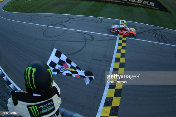 Martin Truex Jr driver of the Bass Pro Shops/Tracker Boats Toyota crosses the finish line to win the Monster Energy NASCAR Cup Series Hollywood...