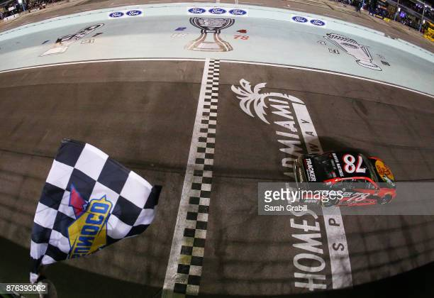 Martin Truex Jr driver of the Bass Pro Shops/Tracker Boats Toyota crosses the finish line to win the Monster Energy NASCAR Cup Series Championship...