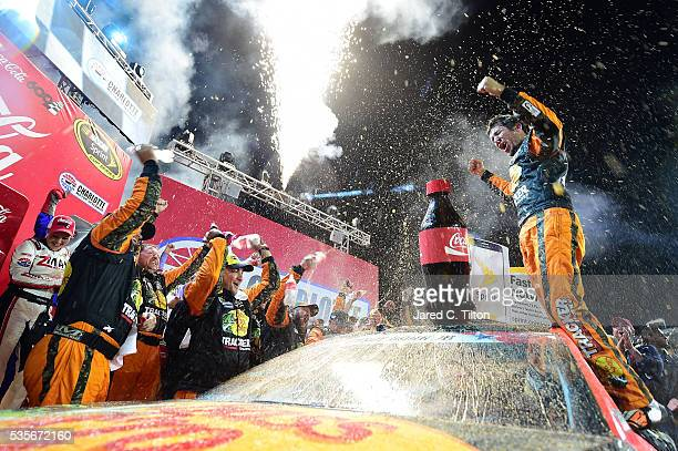 Martin Truex Jr driver of the Bass Pro Shops/Tracker Toyota celebrates in Victory Lane after winning the NASCAR Sprint Cup Series CocaCola 600 at...