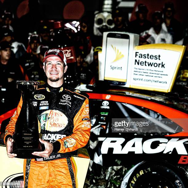 Martin Truex Jr driver of the Bass Pro Shops/Tracker Toyota poses with the trophy in Victory Lane after winning the NASCAR Sprint Cup Series CocaCola...
