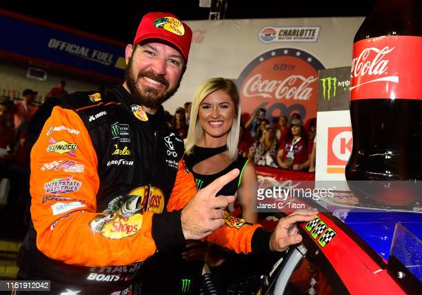 Martin Truex Jr driver of the Bass Pro Shops/TRACKER/USO Toyota applies the winner's sticker after the Monster Energy NASCAR Cup Series CocaCola 600...