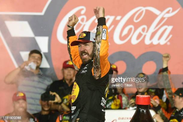 Martin Truex Jr driver of the Bass Pro Shops/TRACKER/USO Toyota celebrates in Victory Lane after winning the Monster Energy NASCAR Cup Series...