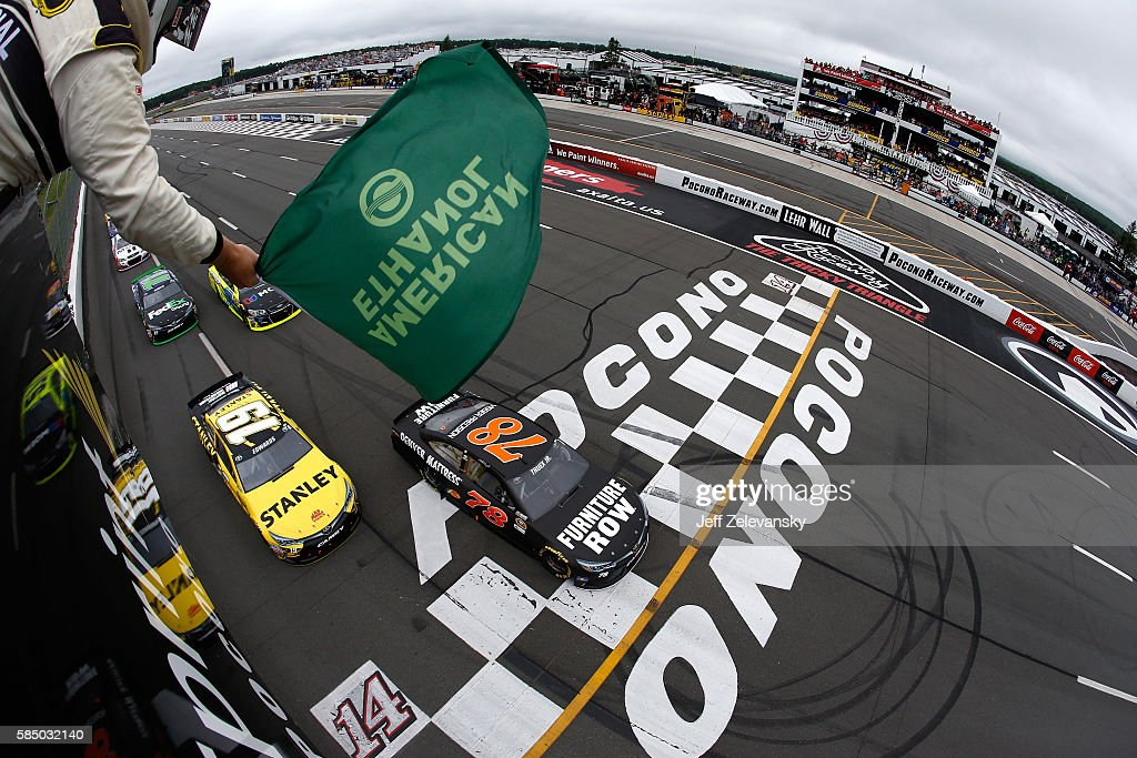 Martin Truex Jr, driver of the #78 Furniture Row Toyota, and Carl Edwards, driver of the #19 Stanley Toyota, lead the field to the green flag to start the NASCAR Sprint Cup Series Pennsylvania 400 at Pocono Raceway on August 1, 2016 in Long Pond, Pennsylvania. The race was delayed due to inclement weather on Sunday, July 31.