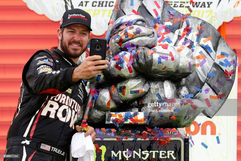 Martin Truex Jr., driver of the #78 Furniture Row/Denver Mattress Toyota, takes a selfie with the trophy in Victory Lane after winning the Monster Energy NASCAR Cup Series Tales of the Turtles 400 at Chicagoland Speedway on September 17, 2017 in Joliet, Illinois.