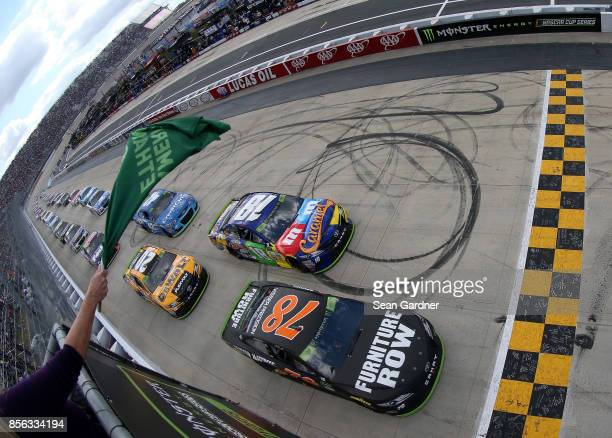 Martin Truex Jr driver of the Furniture Row/Denver Mattress Toyota and Kyle Busch driver of the MM's Caramel Toyota lead the field to the green flag...