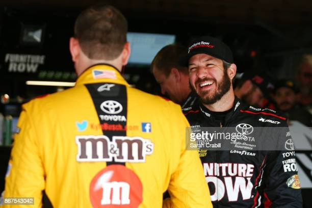 Martin Truex Jr driver of the Furniture Row/Denver Mattress Toyota and Kyle Busch driver of the MM's Halloween Toyota talk in the garage before...