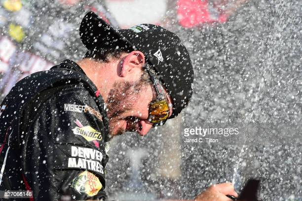 Martin Truex Jr driver of the Furniture Row/Denver Mattress Toyota celebrates by spraying champagne in Victory Lane after winning the Monster Energy...