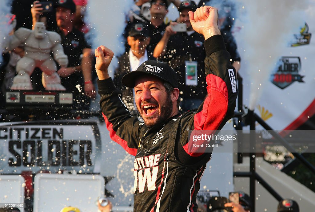 Martin Truex Jr., driver of the #78 Furniture Row/Denver Mattress Toyota, celebrates in Victory Lane after winning the NASCAR Sprint Cup Series Citizen Solider 400 at Dover International Speedway on October 2, 2016 in Dover, Delaware.