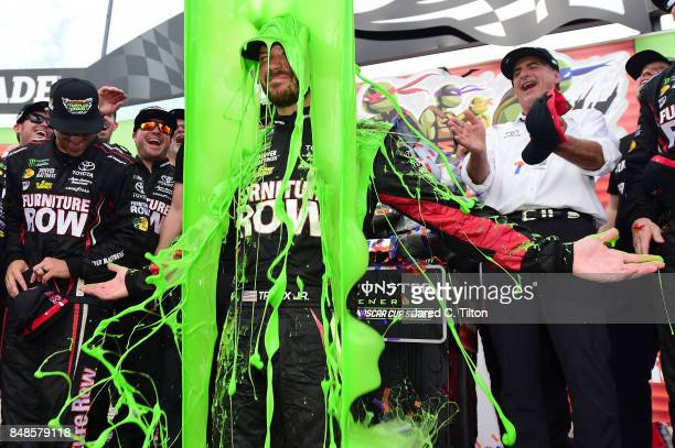 Martin Truex Jr driver of the Furniture Row/Denver Mattress Toyota celebrates in Victory Lane as he gets 'slimed' after winning the Monster Energy...