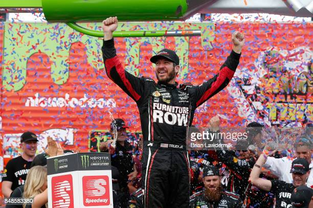 Martin Truex Jr driver of the Furniture Row/Denver Mattress Toyota celebrates in victory lane after winning during the Monster Energy NASCAR Cup...