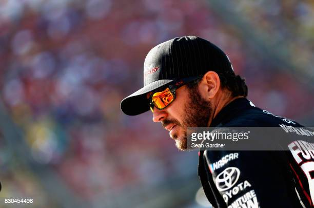 Martin Truex Jr driver of the Furniture Row/Denver Mattress Toyota stands on the grid during qualifying for the Monster Energy NASCAR Cup Series Pure...