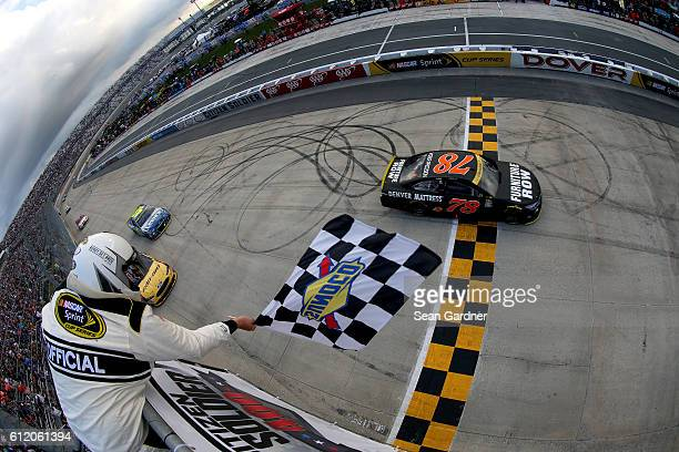 Martin Truex Jr driver of the Furniture Row/Denver Mattress Toyota takes the checkered flag to win the NASCAR Sprint Cup Series Citizen Solider 400...