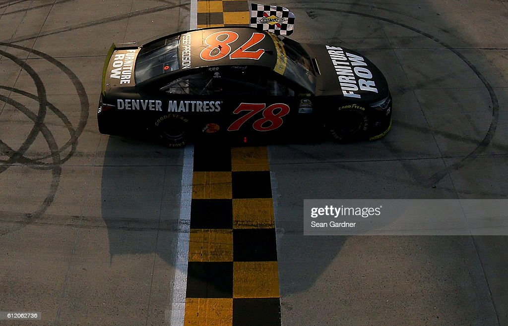 Martin Truex Jr., driver of the #78 Furniture Row/Denver Mattress Toyota, celebrates with the checkered flag after winning the NASCAR Sprint Cup Series Citizen Solider 400 at Dover International Speedway on October 2, 2016 in Dover, Delaware.