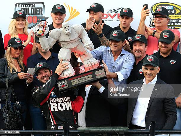 Martin Truex Jr driver of the Furniture Row/Denver Mattress Toyota celebrates with the trophy in Victory Lane after winning the NASCAR Sprint Cup...