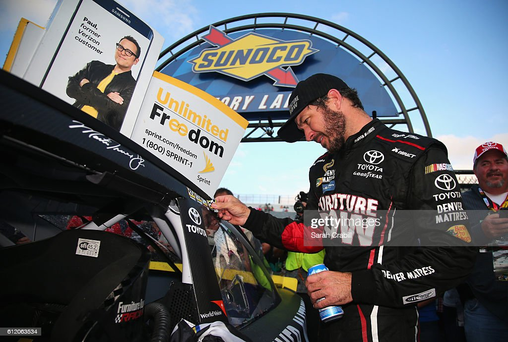 Martin Truex Jr., driver of the #78 Furniture Row/Denver Mattress Toyota, affixes the winner's decal to his car in Victory Lane after winning the NASCAR Sprint Cup Series Citizen Solider 400 at Dover International Speedway on October 2, 2016 in Dover, Delaware.