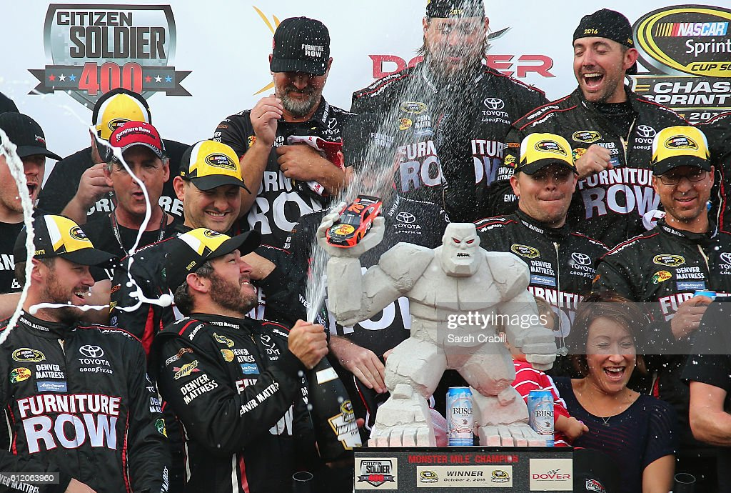 Martin Truex Jr., driver of the #78 Furniture Row/Denver Mattress Toyota, celebrates with the trophy in Victory Lane after winning the NASCAR Sprint Cup Series Citizen Solider 400 at Dover International Speedway on October 2, 2016 in Dover, Delaware.