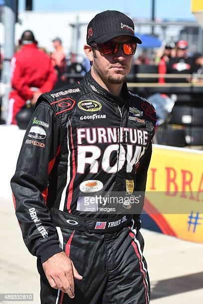 Martin Truex Jr driver of the Furniture Row/Visser Precision Chevrolet walks on the grid prior to the NASCAR Sprint Cup Series myAFibRiskcom 400 at...