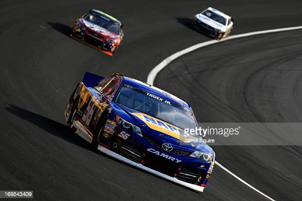 Martin Truex Jr driver of the NAPA Auto Parts Toyota leads a group of cars during the NASCAR Sprint Cup Series CocaCola 600 at Charlotte Motor...