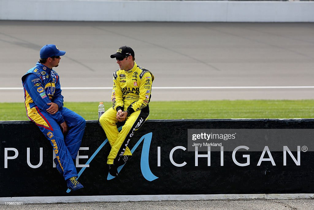 Martin Truex Jr., driver of the #56 NAPA Auto Parts Toyota, talks with Matt Kenseth, driver of the #20 Dollar General Toyota, on the grid during qualifying for the NASCAR Sprint Cup Series 44th Annual Pure Michigan 400 at Michigan International Speedway on August 16, 2013 in Brooklyn, Michigan.