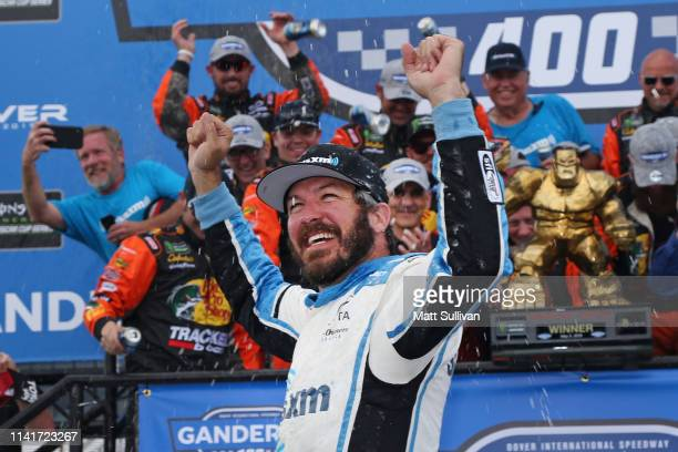 Martin Truex Jr driver of the SiriusXM Toyota celebrates in Victory Lane after winning the Monster Energy NASCAR Cup Series Gander RV 400 at Dover...