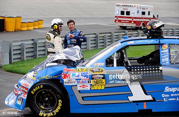 Martin Truex Jr driver of the Vaseline MEN Body Lotion Chevrolet talks with an official after being involved in a crash during the NASCAR Sprint Cup...