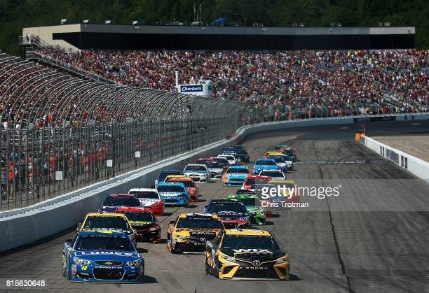 Martin Truex Jr driver of the WIX Filters Toyota and Jimmie Johnson driver of the Lowe's Chevrolet lead the field into turn one after taking the...