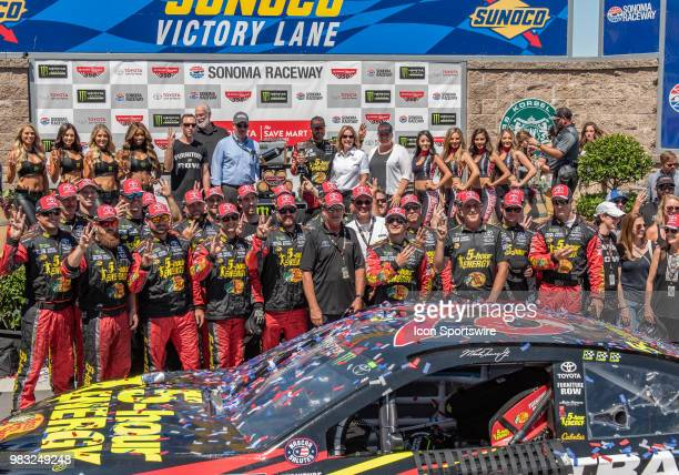 Martin Truex Jr driving the # Toyota for Furniture Row Racing and his crew show their victory count in Victory Lane after winning the Toyota/Save...