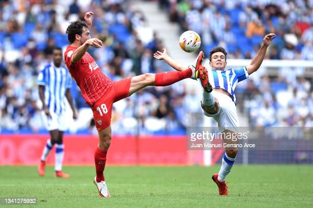 Martin Zubimendi of Real Sociedad and Thomas Delaney of Sevilla battle for possession during the La Liga Santander match between Real Sociedad and...