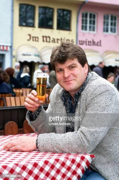 """Martin Zuhr, Moderator der RTL-Comedy-Talkshow """"TV Kaiser"""" bei einem Kölsch in einem Biergarten durch die Altstadt von Köln, Deutschland 1997."""