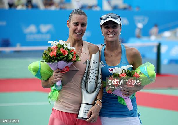 Martina Hingis of Switzerland and Flavia Pennetta of Italy pose with the trophy after winning their doubles final match against Cara Black of...