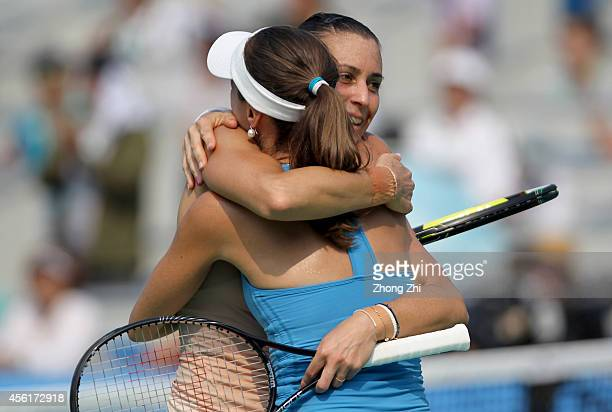 Martina Hingis of Switzerland and Flavia Pennetta of Italy react after winning their doubles final match against Cara Black of Zimbabwe and Caroline...