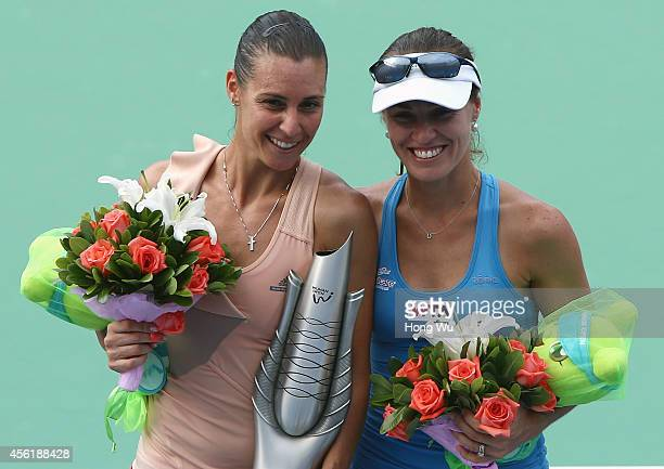 Martina Hingis of Switzerland and Flavia Pennetta of Italy victorious with trophy after winning their doubles final match against Cara Black of...