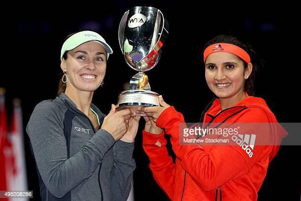 Martina Hingis of Switzerland and Sania Mirza of India hold up the Martina Navratilova Doubles Trophy after defeating Carla Suarez Navarro and...