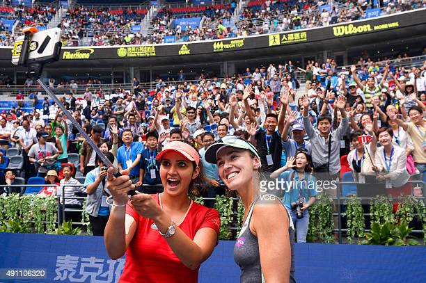 Martina Hingis of Switzerland and Sania Mirza of India take a selfie with fans after winning the doubles final match against IrinaCamelia Begu of...
