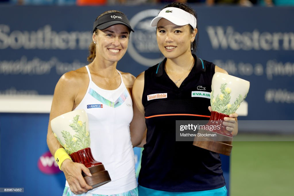 Martina Hingis of Switzerland and Yung-Jan Chan of Taipei pose for photographers with the winner's trophy after defeating Su-Wei Hsieh of Taipei and Monica Niculescu of Romania in the women's double final during day 8 of the Western & Southern Open at the Lindner Family Tennis Center on August 19, 2017 in Mason, Ohio.