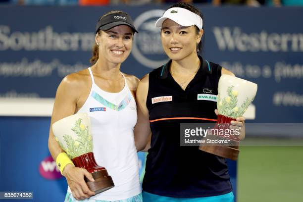 Martina Hingis of Switzerland and YungJan Chan of Taipei pose for photographers with the winner's trophy after defeating SuWei Hsieh of Taipei and...