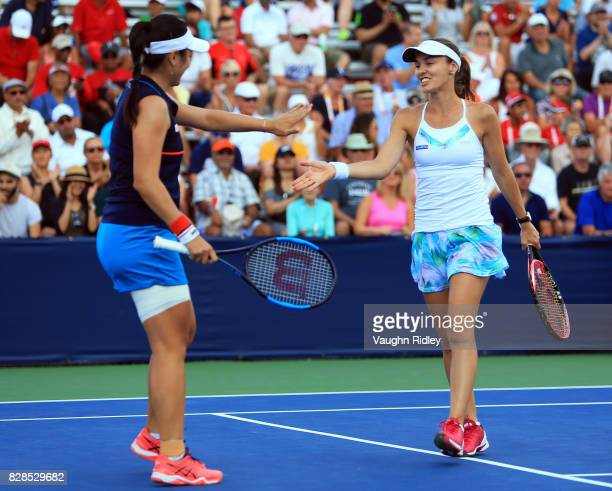 Martina Hingis of Switzerland high fives her doubles partner YungJan Chan of Chinese Taipei after winning a point against Andreja Klepac of Slovenia...