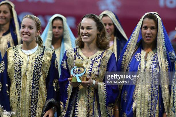 Martina Hingis of Switzerland holds the trophy of the Qatar Open 2004 as she poses with fellow tennis players world number one Justine HeninHardenne...