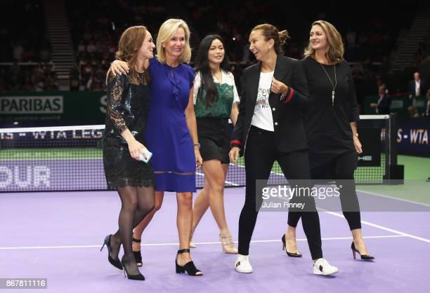 Martina Hingis of Switzerland leaves the court with Micky Lawler WTA President Chan YungJan of Chinese Taipei and WTA Legend Ambassadors Iva Majoli...