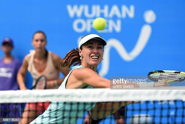 Martina Hingis of Switzerland reaches for a return as partner Flavia Pennetta of Italy looks on during their women's doubles semifinal win over...