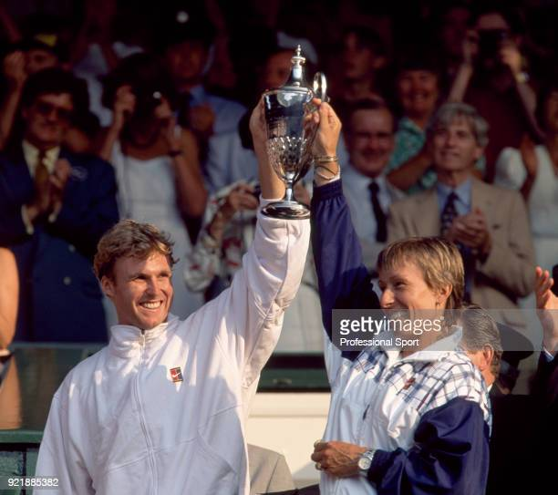 Martina Navratilova and Jonathan Stark of the USA lift the trophy after defeating Gigi Fernandez of the USA and Cyril Suk of the Czech Republic in...