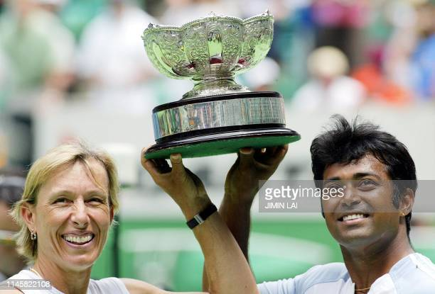 Martina Navratilova of the US and partner Leander Paes of India hold up the winner's trophy following their win in the mixed doubles final at the...