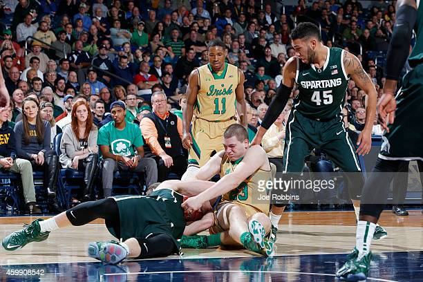 Martinas Geben of the Notre Dame Fighting Irish battles for a loose ball against Matt Costello of the Michigan State Spartans during the ACC/Big Ten...