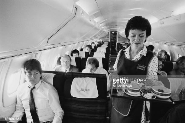 Martine, a flight attendant, serving meals on a British Airways Concorde, UK, 31st August 1983.