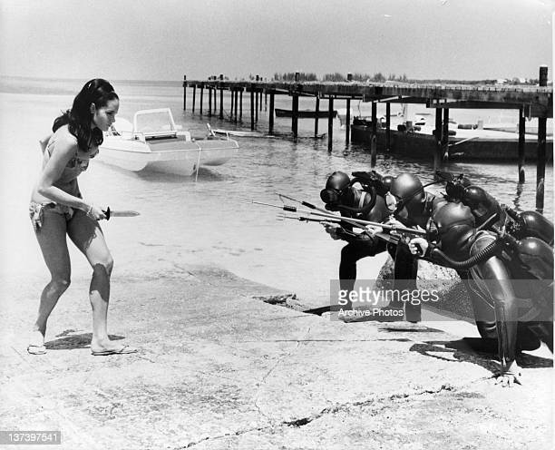 Martine Beswick assigned to help a british agent faces a group of spectre frogmen in a scene from the film 'Thunderball' 1965
